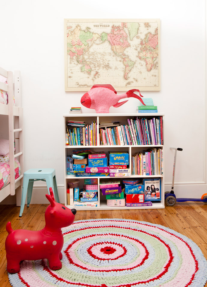 From the girls' bedroom wall, a canvas map from Typo tells tales of faraway countries. The bright mat is a crochet T-shirt work found at Merry Pop Ins, and the fish is from Heartworks, bought when Cara was pregnant with Idana.