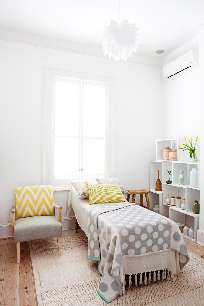 The treatment room is neutral without being clinical. The treatment bed is covered in a cream bamboo throw from Cotton Throws and a playful polka-dotted throw from Country Road, and it stands on a wool rug from Hertex.