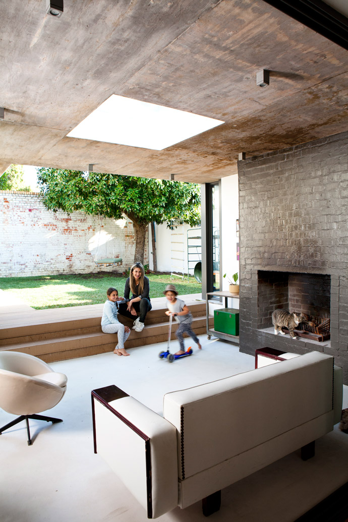 Having fun on the sunken veranda are Cara and her daughters Idana (front) and Mira, while Nelson the cat checks out the activities from the safety of the large fireplace. The solid concrete roof with its square skylight extends across the brand-new added kitchen and lounge extension.
