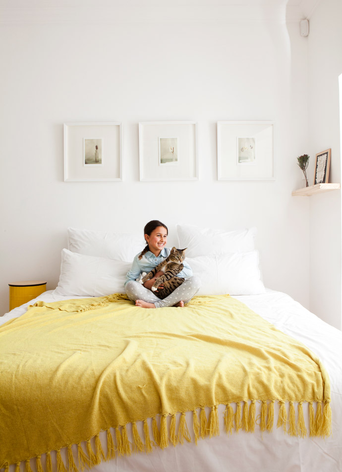 Idana keeps Nelson company in her parents' bedroom. The three prints on the wall are from Haas and the side table is from Pedersen and Lennard.  The yellow throw is a Woolies favourite.
