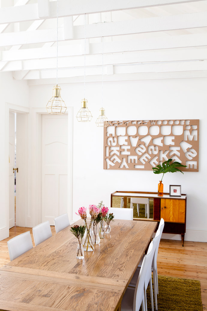 Like the rest of the house's lighting, these authentic copper light fittings above the Coricraft dining table and chairs are the work of Cara's father-in-law, Bernard Saven from Lightworld. The wall above a vintage cabinet is the new home of a SupaWood laser-cut panel Cara rescued from a printer's rubbish heap.