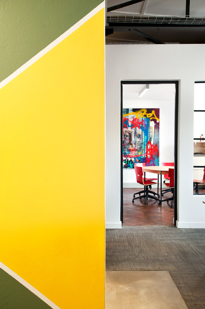 Colour-blocked walls are an ever-changing visual thread that connects the many buildings and spaces. The table is by Pedersen and Lennard andthe red chairs by RAW Studios. Artwork: Kilmany-Jo Liversage, Untitled, acrylic paint and aerosol spray on canvas.