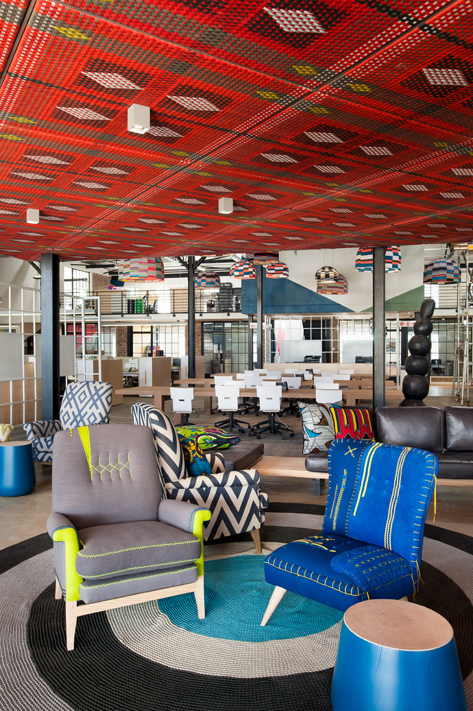 A ceiling of brightly woven panels by John Vogel overlooks chairs by Casamento, a couch and stools by GOET Furniture and Design and a carpet by Fibre Designs. In the background, hotdesks by David Krynauw and chairs by RAW Studios are for use by the Central Kitchen team as well as visitors.