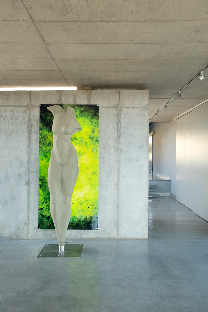 A sensual sculpture in the foyer is beautifully offset against the printed glass artwork and raw concrete wall beyond – a bold homage to the sculptural beauty of natural concrete.