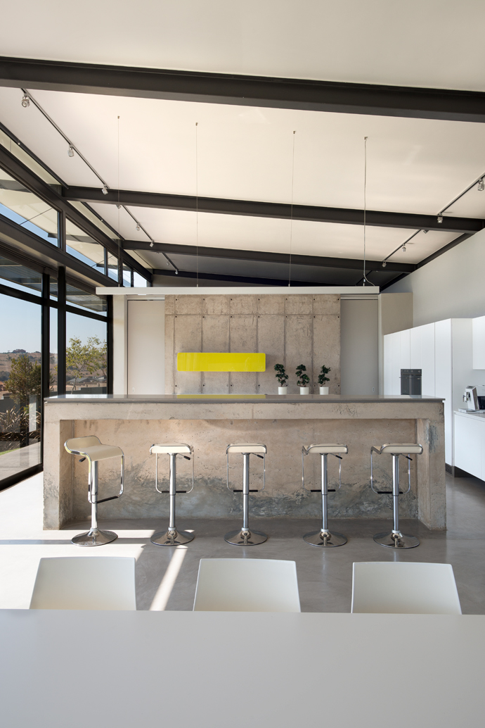 The natural beauty of concrete, steel and glass are combined in infinite variations of raw, textured and polished finishes to create the crisp and clean-cut interior style. The bar stools at the kitchen counter, dining room table and chairs are all from Spazio.