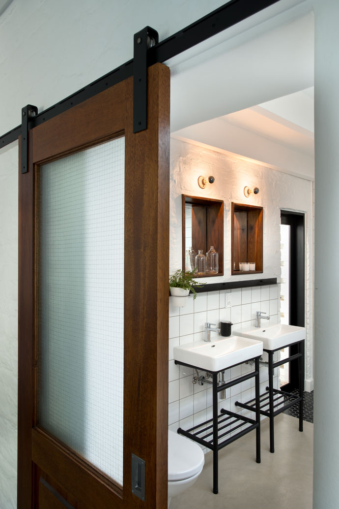 The siding doors add an industrial feel to the bathroom. One of Nico's favourite accessories in this room is the black liquid soap dispenser from Yuppiechef. The basin pedestals and shelving are by MuseContracts.