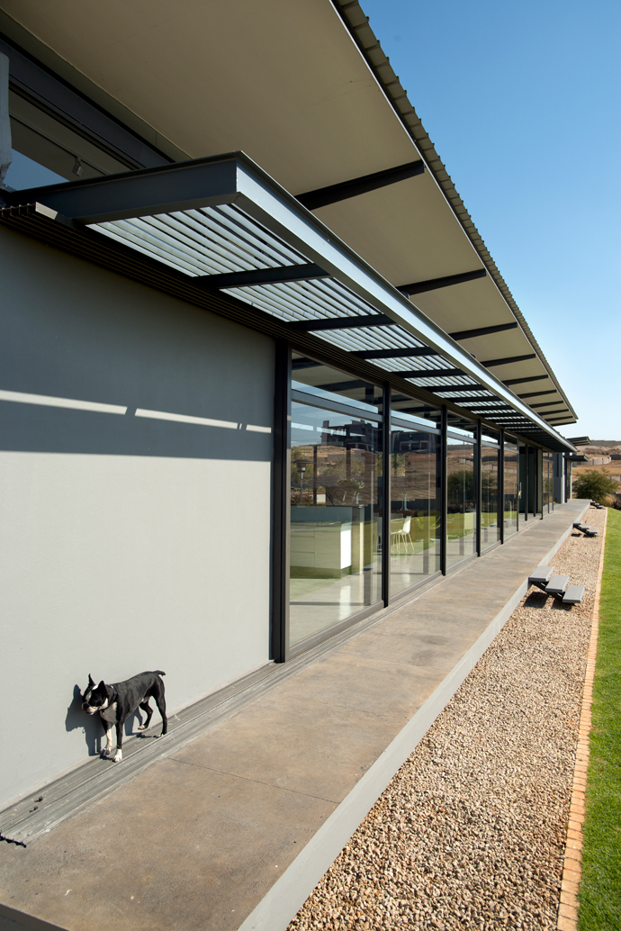 Designed specifically with the Bushveld climate in mind, the slatted steel screens and generous roof overhangs protect the floor-to-ceiling glass sliding doors − and the family pooch, Dino − against the blazing summer sun, while allowing full access to sunlight during the chilly winter months.