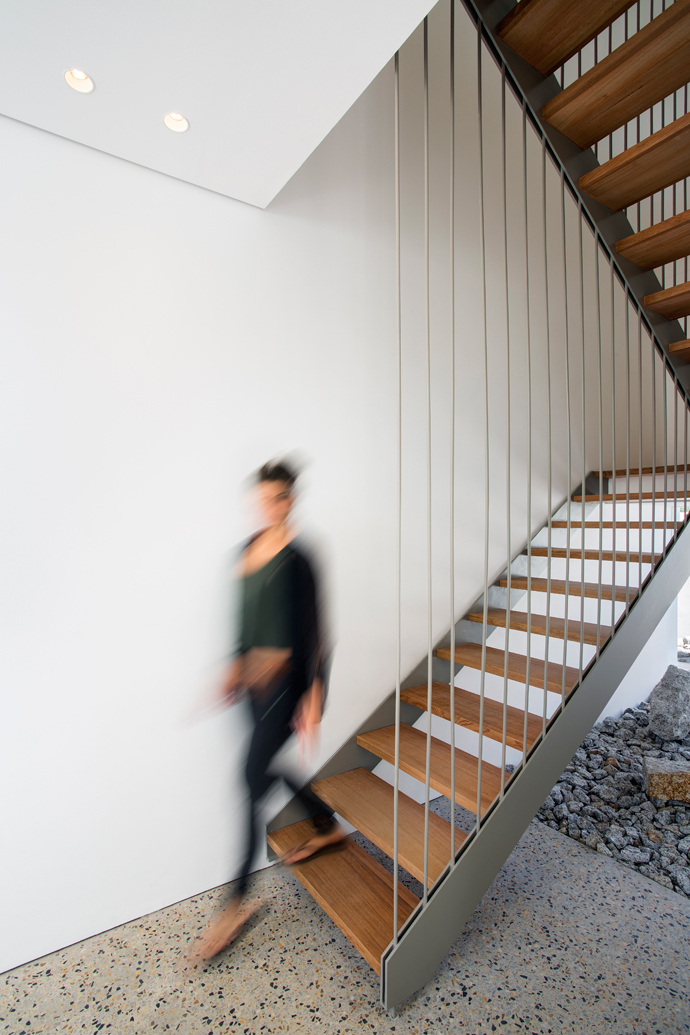 A steel-and-timber staircase is suspended from the ceiling by steel rods.