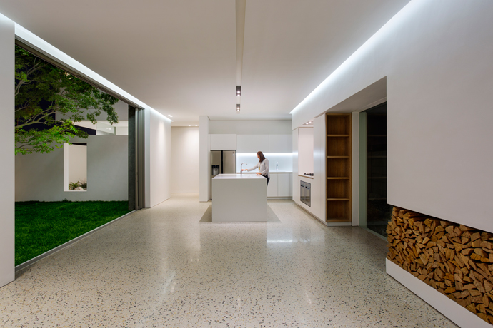 Clean lines characterise this minimalist home. The wall that forms the back of the living space houses the fireplace and the kitchen cooking zone. The flooring is polished concrete with selected aggregate colours and sizes.