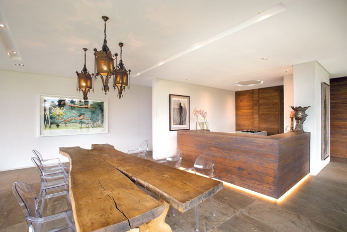 "The dining table is one of only two tables made from an old oak tree struck down by lightning; the owners say they ""begged it off the Everard Read Gallery"". The Louis Ghost chairs are from Spazio. The artwork on the left is by Beezy Bailey and the one behind the kitchen counter by Deborah Bell."