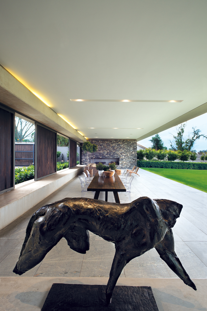 The striking sculpture on the patio is abronze by Stellenbosch-based artist Dylan Lewis. The dining table is from ThePrivate House Company and the Louis Ghost chairs from Spazio.