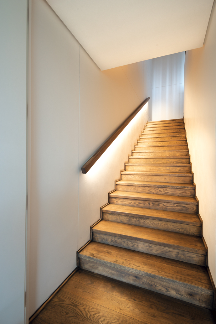The staircase and the upstairs flooring is oiled oak. LED lighting under the handrail gives off a soft light.