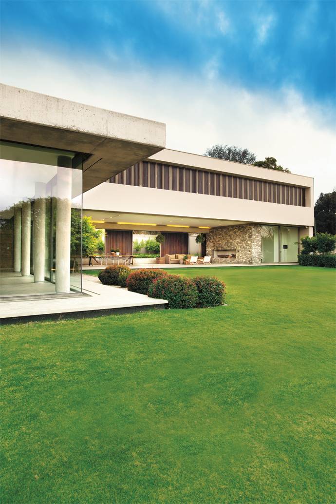 Screens of solid meranti wood and off-shutter concrete walls and columns contrast with the smooth glass. Sliding doors lead out to abeautifully landscaped lawn.