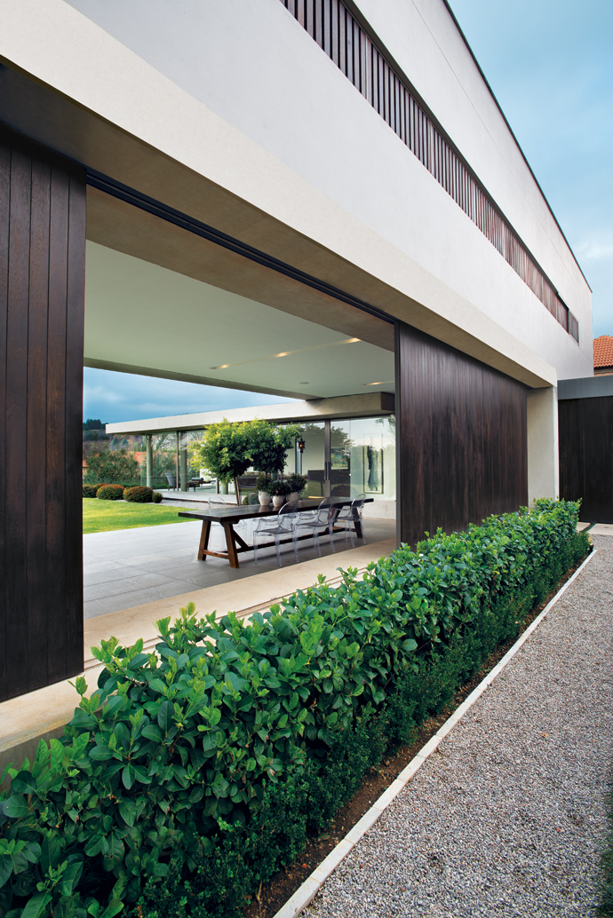A hedge separates the wide gravel motor court from the patio, conveying a concrete Zen vibe.