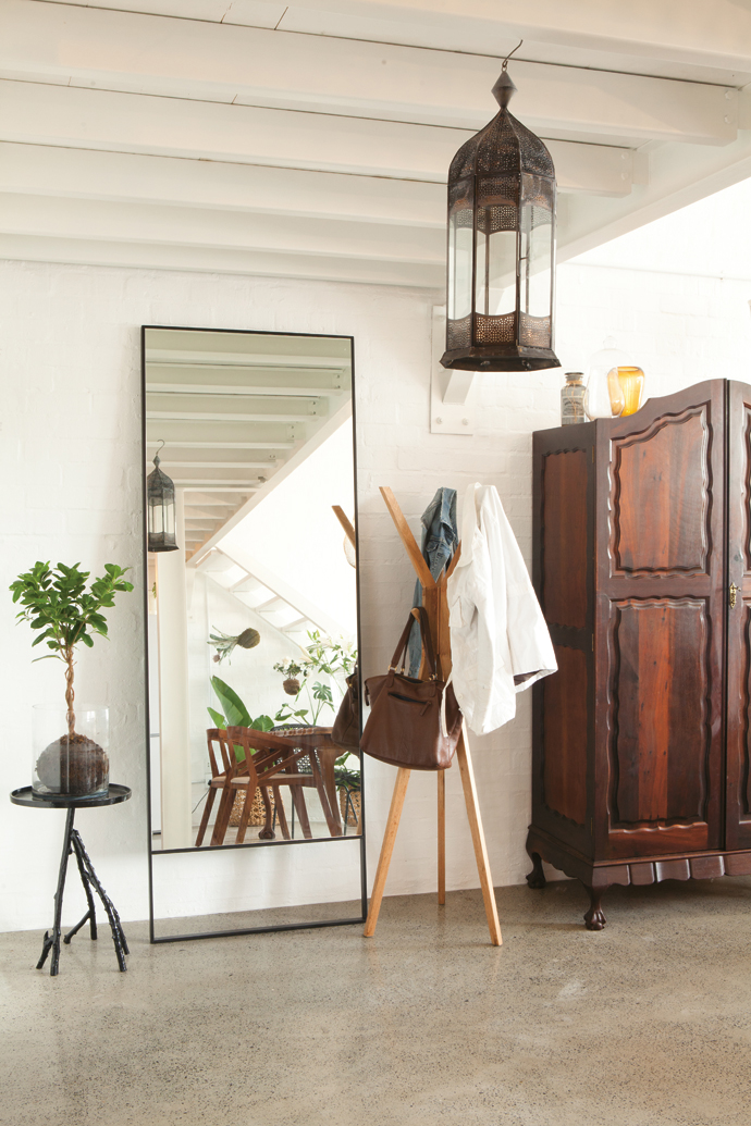 A cut-out metal lantern Lize bought in Mexico on a buying trip and a vintage family wardrobe and branch-legged side table from @homelivingspace reveal atouch ofwhimsy.