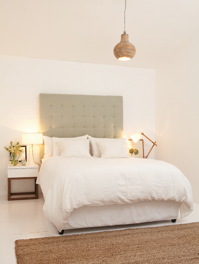 The bedroom's muted tones and earthy touches make for a calming space. Lize made the sage-green padded headboard herself, and the bedside tables are from @homelivingspace. The wooden pendant light is from India.
