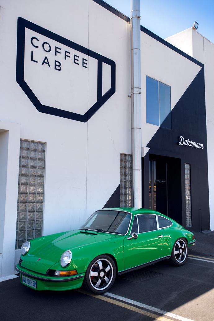 A 1970 Porsche 911 in front of the showroom, which houses both Coffee Lab and the Dutchmann workspace and showroom.