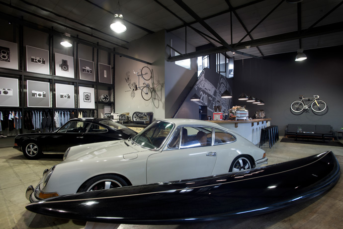 "In the foreground is a 1968 Porsche 912 Weekend Racer and behind it a 1971 Porsche 911 T. Classic and contemporary Faema coffee machines are on display alongside Dutchmann's ""Iconic Camera Poster Portfolio"", comprising 10 iconic film cameras that have made a remarkable contribution to photography."