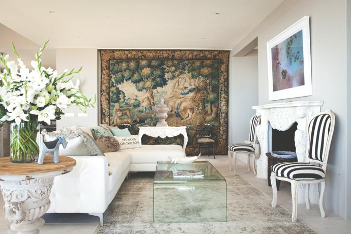A 17th-century Aubusson tapestry, fittingly entitled Summer, dominates the entrance to the lounge area. The elaborately carved stone mantelpiece was bought many years ago at Plaster Art in Cape Town and was kept wrapped up until it found its rightful place around the fireplace of the new West Coast home. The hearth is flanked by two gessoed Louis XIV-style chairs that have been upholstered in black-and-white fabric from Pierre Frey in Paris. Above the fireplace is adistinctive pastel painting by Louis. The glass coffee table from @Home Living stands on arug imported from Belgium by Hertex. The stoneware schnauzer is the work of ceramist Janet Lightbody.