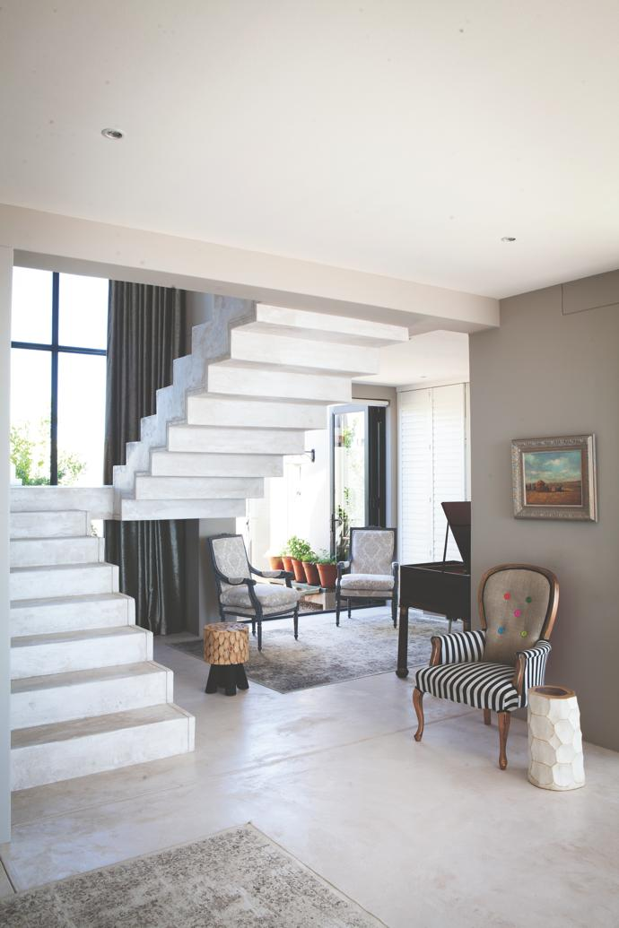 The cantilevered concrete staircase has the same white cement finish as the floors and verandas throughout the house. The striped retro fauteuil is from The Showroom in Stellenbosch. Above the chair is a late French Impressionist painting of abeach scene at Deauville.