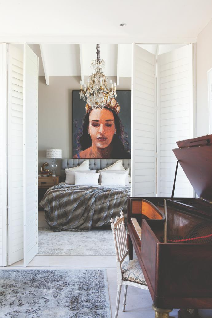White plantation shutters open into the guest bedroom, where one of Louis's gigantic portraits of Christine van Wyk hangs above the bed. An 18th-century French chandelier found at the famous Parisian auction house Drouot illuminates the space. The piano is arare Sébastien Érard instrument that bears its creator's signature and the date 1828.