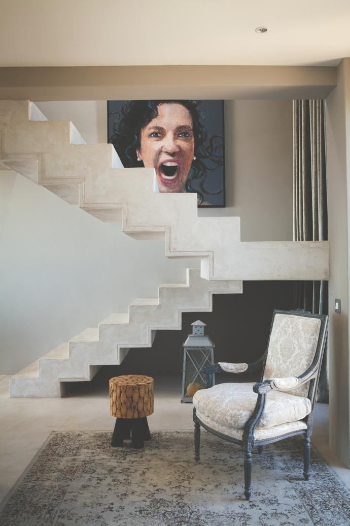 The dramatic staircase zigzags past another of Louis's large-scale portraits. On the carpet is asquare-backed French LouisXIV-style bergère chair,upholstered incotton-and-silkdamask.