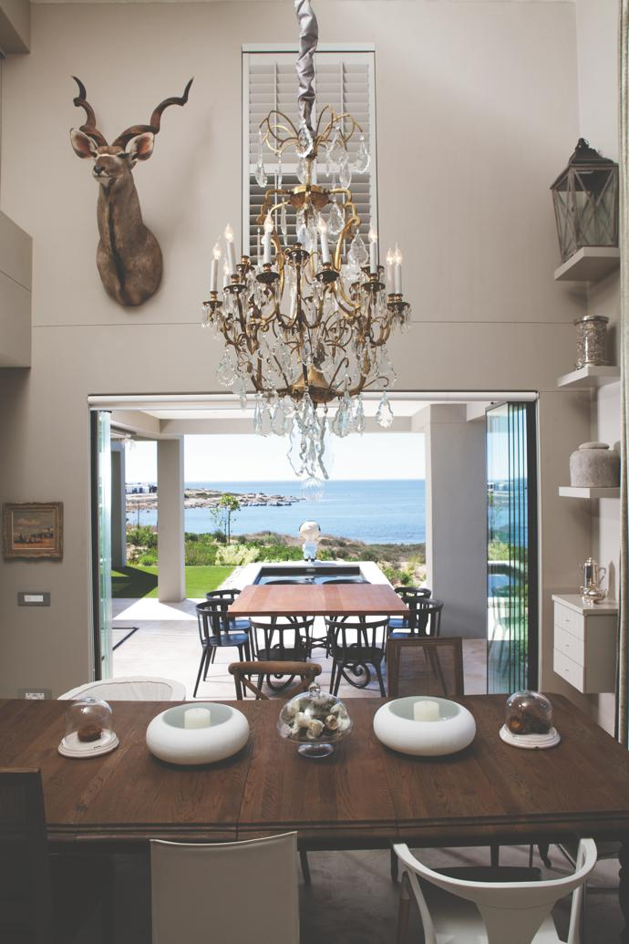 The double-volume dining room is dominated by a kudu trophy from Hardy's native Namibia. The spectacular chandelier comes from a demolished villa in Zamalek on Gezira Island in the Nile River. The frameless glass doors open onto the main patio, overlooking the swimming pool and Kaloenie's Bay