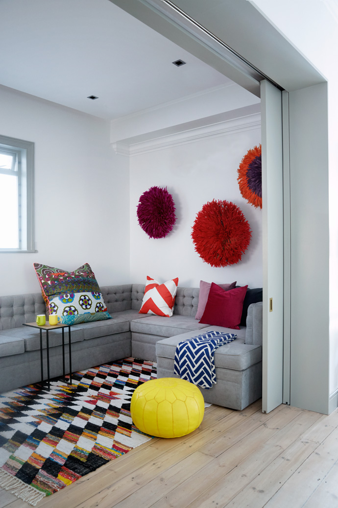 Bamiléké feather headdresses adorn one wall of the TV room. The sofa is covered in Hertex grey velvet and the scatter cushions are from Big Blue. The yellow pouffe was specially imported by Moroccan Warehouse.
