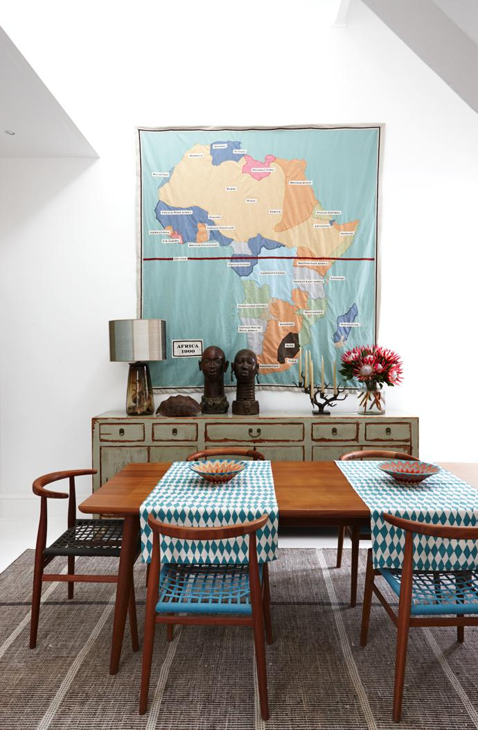 The map depicting Africa in the 1900s was hand-made by Thomas. The sideboard is from Gilles Botbyl, the bronze heads were bought in Benin, the table and chairs are by Vogel and the table runners are by Skinny laMinx. The rug is from Mae Artisan Rugs.