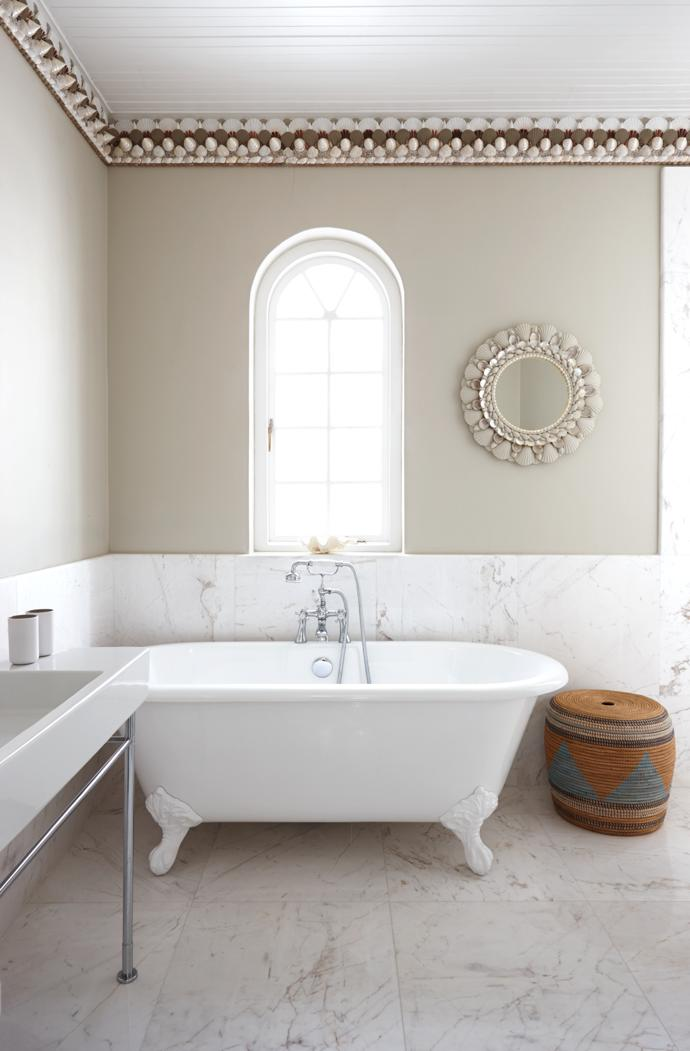 The white marble wall treatment was created by the couple's builder, Team Austin. The bath is by Victorian Bathrooms and the laundry basket is from Weylandts. Thomas made the ornate cornices and the framed mirror.