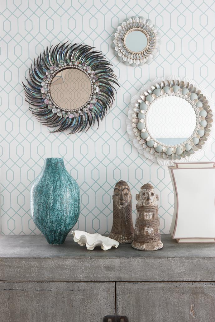 In this arrangement, three Thomas Boog shell-framed mirrors are mounted on wallpaper by La Farge in the United States. The vase is by local sculptor Chantel Woodman and the clay figurines are from Robert Sherwood Design.