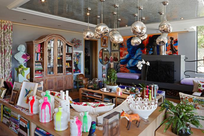 In the lounge, Tom Dixon's chrome Melt pendants dangle above Graham and Green dripping neon vases. The Shakespeare Orchid bust by Jimmie Martin perches next to the book case and a Lionel Smit portrait dominates the back wall.