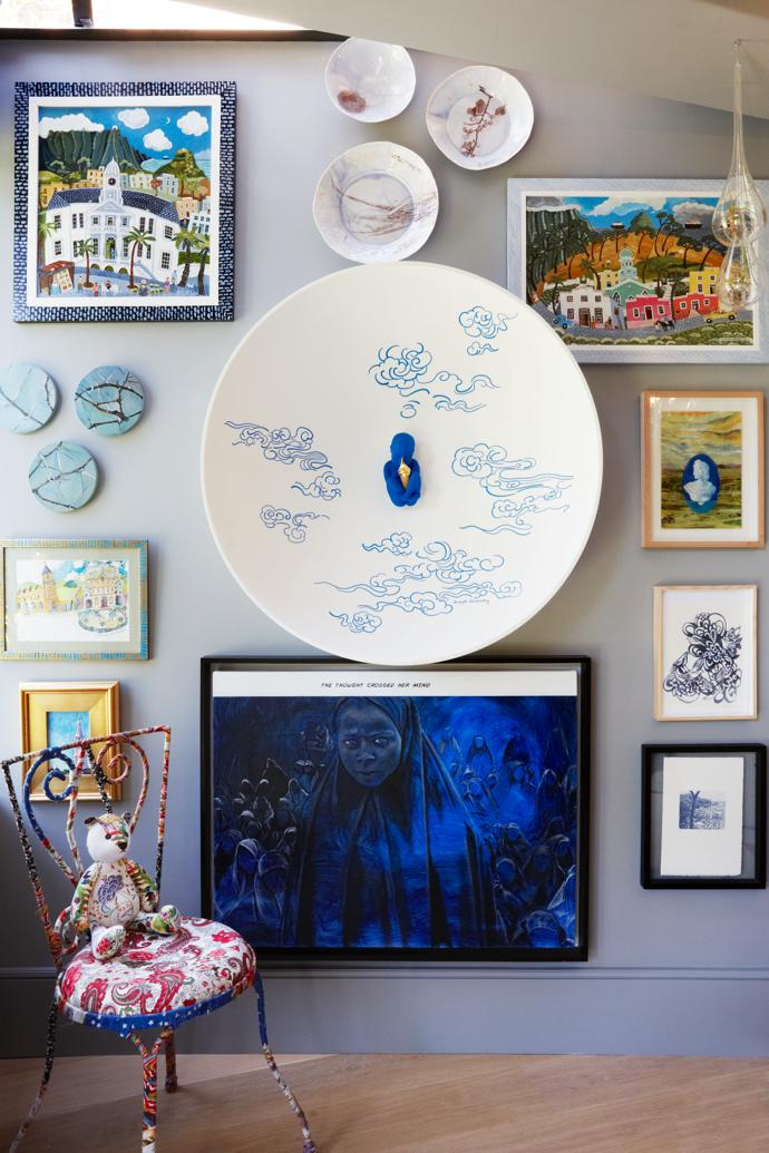 Berdine's love of art is reflected everywhere in the house. Focal points on this downstairs bedroom wall are Joseph Klibansky's blue baby sculptural work Dream Clouds, and Boko Harem by Catherine Ocholla. In the foreground, a hand-made bear from Heartworks perches on a Debenhams UK chair.