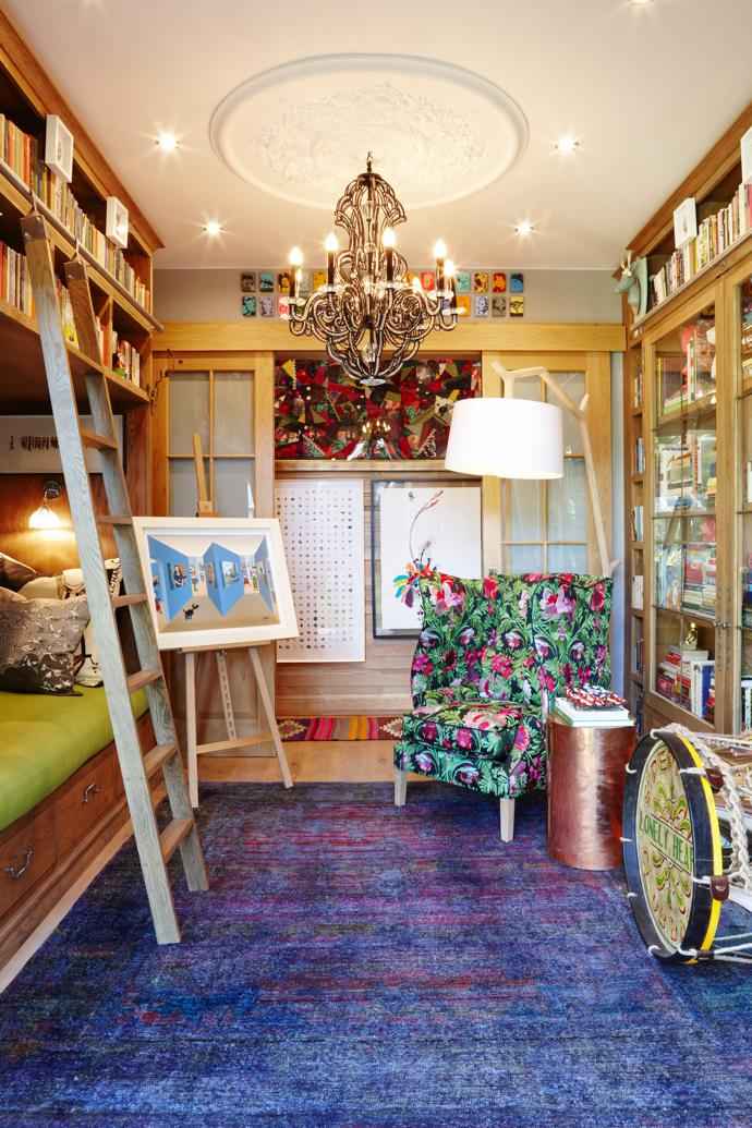 The library doubles as a bedroom. On the easel is John Wilson's Master I. The floral chair is by Moorgas & Sons, upholstered in Christian Lacroix Bataille de Fleur Bougainvillier, and the Sergeant Pepper Drum is by Andrew Martin. The chandelier is from One on One Gallery, and the Impressionist-style rug is by ABC Carpet and Home in New York.