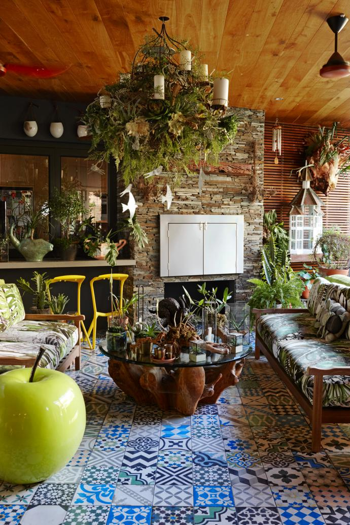Cool, kitsch and quirky meet Mother Nature on the large veranda. The coffee table is from Weylandts and the foliage candelabra above is by Craig Olckers from Oolong Blue. The giant green apple was found at Equus Cavalli Gallery.