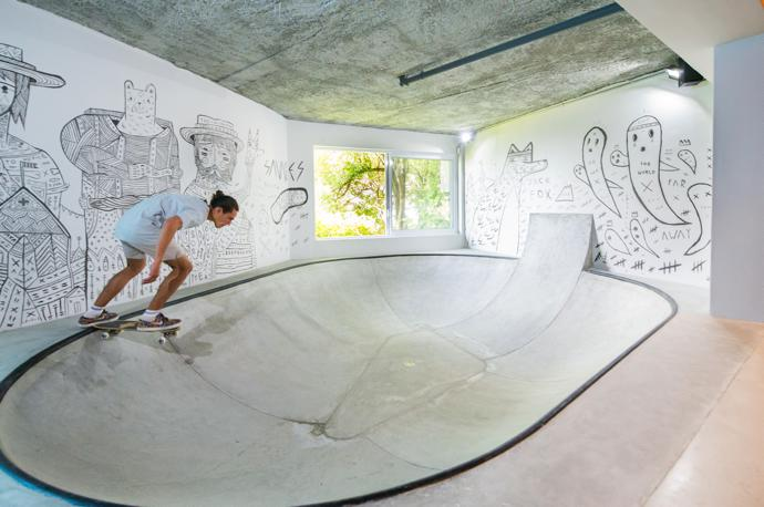 An entire floor level below had to be filled in to create the deep skate bowl. Timber fins were used to create the frame, and flexible plywood and polystyrene to shape the backing. The bowl was then finished in concrete. The mural is by South African street artist Jack Fox.