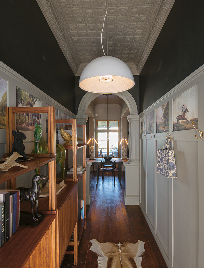 The entrance hall has a strong horse theme. Prints featuring horses from the Rijksmuseum have been inserted into the wall paneling, and a vintage Scandinavian bookcase is perfect for displaying all things equestrian.