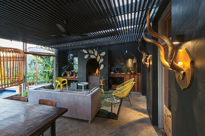 The stoep is an integral part of the house. Large glass doors open up the inside living area to the stoep – an outdoor living area with a fireplace, a dining table and chairs, a sofa and replica Acapulco chairs from Chair Crazy.