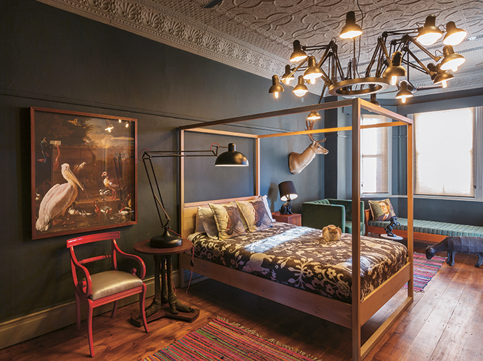 The main bedroom is large and could easily accommodate almost-black walls (Plascon Sushi Wrap) to offset the original pressed ceiling (Dulux Dusted Moss). This starkly masculine bedroom has a modern chandelier and four-poster bed that contrast beautifully with the old print from the Rijksmuseum and a quirky rabbit reading lamp.