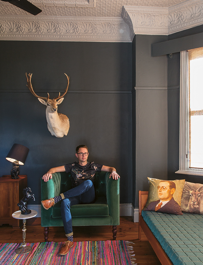 """Etienne, sitting in his bedroom underneath a reindeer head. The entire house is an eclectic tribute to nature. Says Etienne, """"I will never kill an animal for the purpose of taxidermy, so all my stuffed trophies have been recycled from dusty garages and storerooms all over the Western Cape, or bought via Gumtree or at Cash Crusaders."""""""