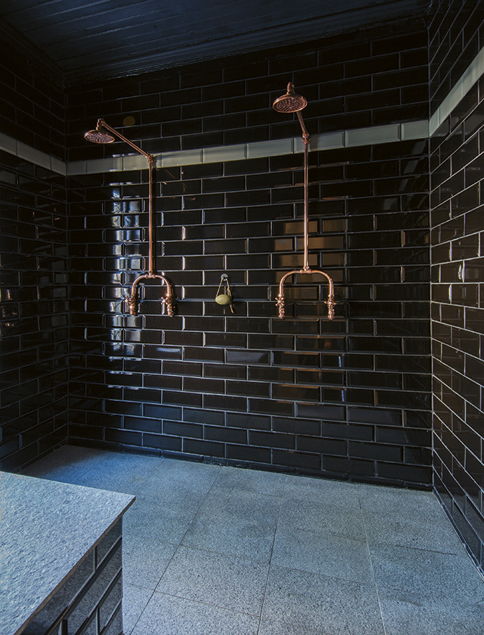 This double shower in the guest bathroom features black metro tiles and copper taps.