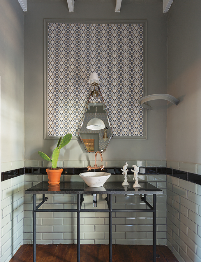A white ceramic basin rests on a custom-made steel vanity in the guest bathroom, where sagegreen metro tiles line the walls and a gold-and-black honeycomb-patterned wallpaper has been inserted into the paneling on the wall behind the mirror.