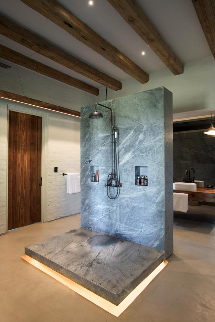 The shower wall in the master suite bathroom is made of leathered granite by Mazista Tiles.