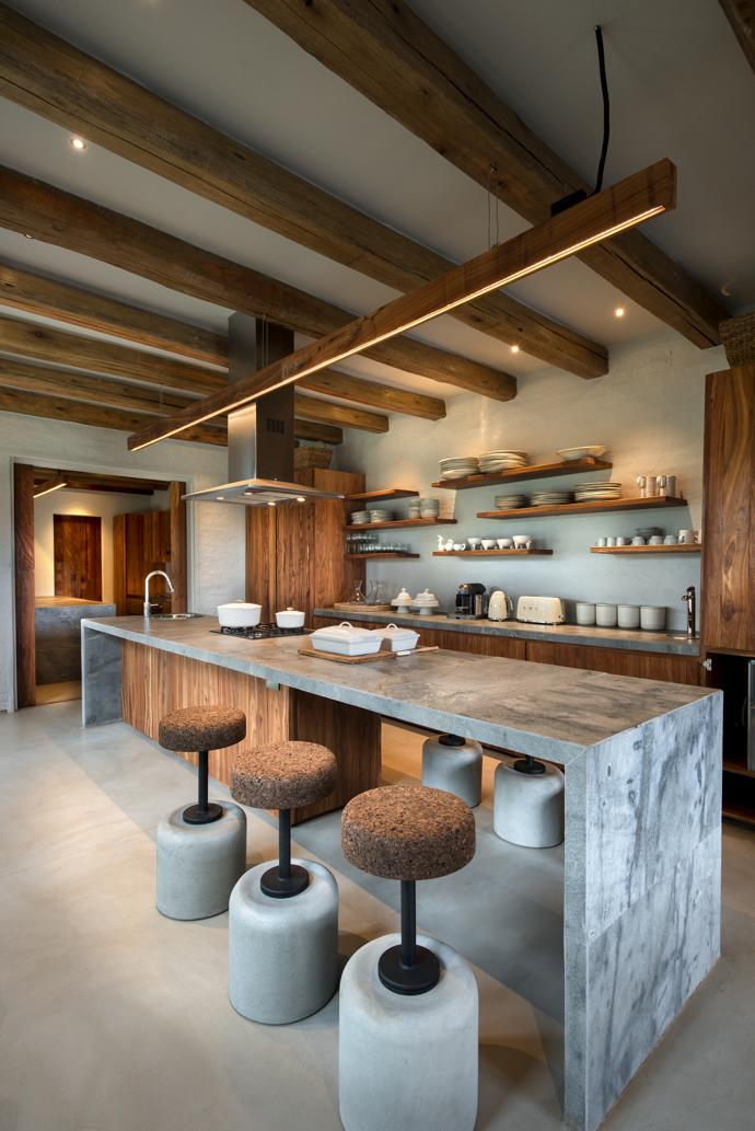 Natural textures abound in the kitchen with its leathered granite tops and cork-and-cement bar stools from Wiid Design. Theoverhead strip lighting is by Streamlight.