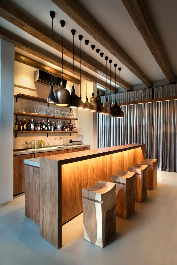 The bar counter and shelving were made by Insitucrete and the wooden turned lights byOne Good Turn. The Harper bar stools are from Weylandts. The glasses and decanters were made by Ngwenya Glass.