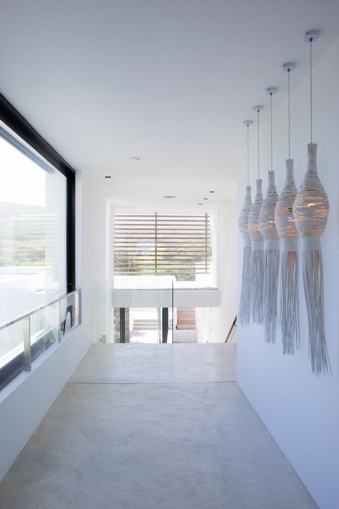The upstairs passage features cane pendant lights from Thailand that the owners dipped in water-based Plascon Velvaglo. The white screed cement-based flooring is by Maxicoatings.