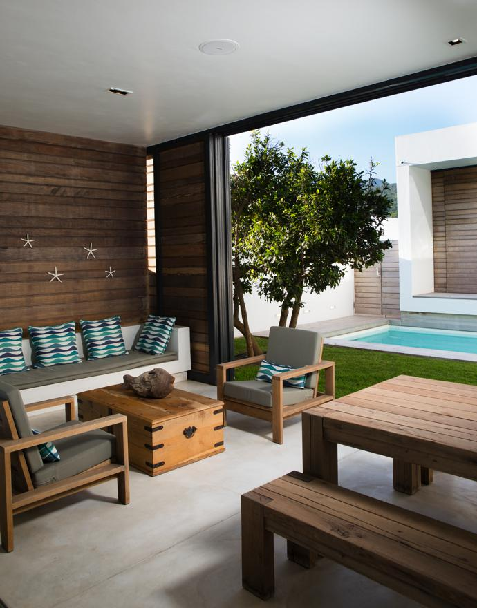 """The solid oak table, benches and chairs on the covered """"stoep"""" adjacent to the courtyard are from Kitchen Inc in Woodstock, and the oak chest is from Pierre Cronje."""