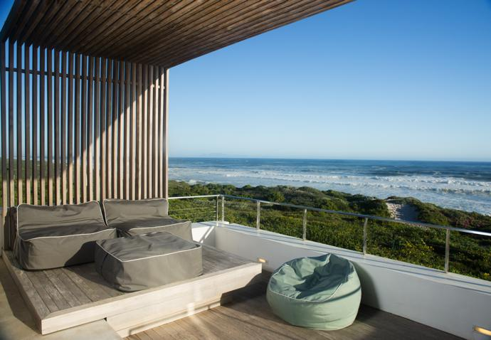 The deck and the pergola are made of bleached and stained limbali timber, which was installed by Coenie Marais Inhouse Finishing. The polished stainless steel balustrade with cable railing is by Chépet Engineering. All the poofs are from Canetime.