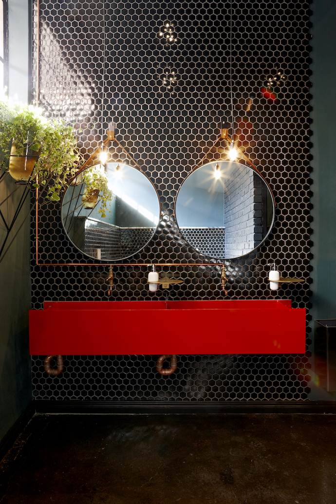 The bathroom basins are made of repurposed I-beams. The plant holder is from Thingking and the two mirrors from Dark Horse. The hexagonal pattern of the floor tiles in the bottle store is continued in the bathroom's scaled-down honeycomb wall tiles.