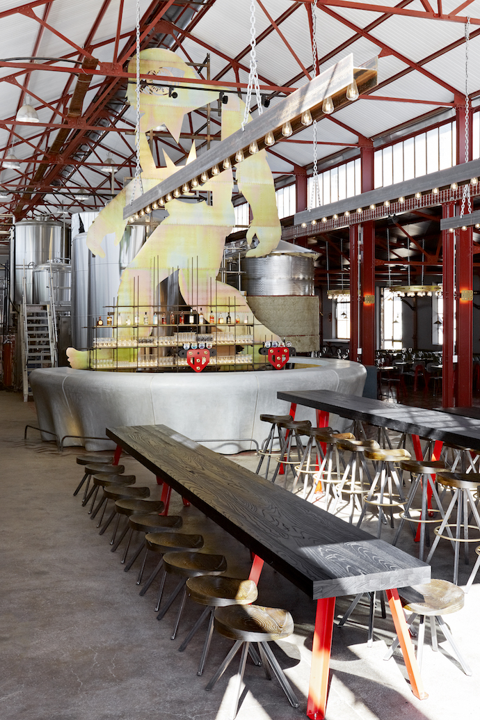Behind the bar, facing the entrance of the brewery, is a 7 m-tall yeti, the brand's icon, made of lasercut yellow zincpassivated steel riveted to a mild steel framework. Haldane Martin Interiors made the tables, choosing black timber to contrast with the red legs, and the swivel stools.